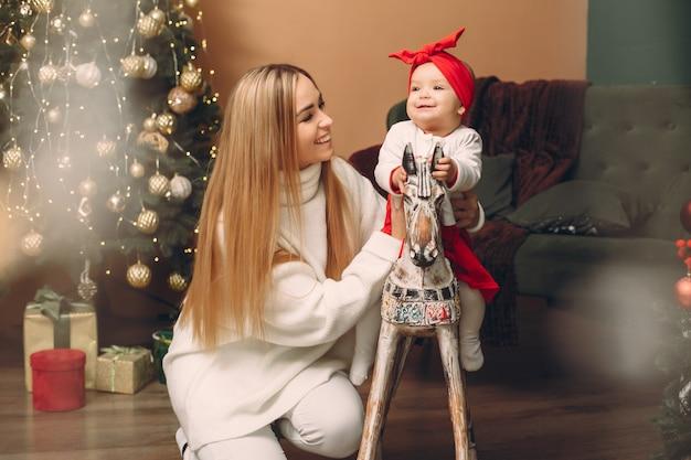 Moeder met schattige dochter in de buurt van de kerstboom