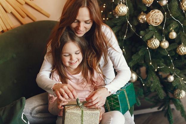 Moeder met schattige dochter in de buurt van kerstboom