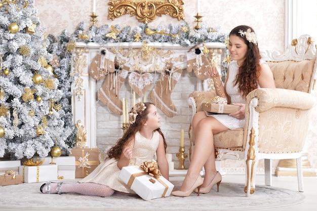 Moeder met schattige dochter poseren in kamer versierd met kerstvakantie
