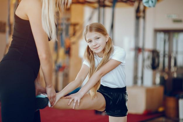 Moeder met schattige dochter sporten in de sportschool