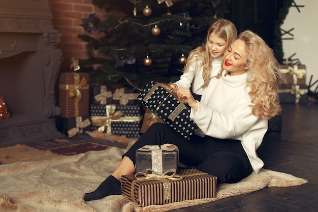 Moeder met schattige dochter thuis in de buurt van kerstboom