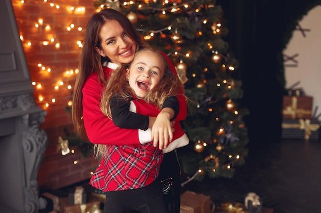 Moeder met schattige dochter thuis in de buurt van open haard