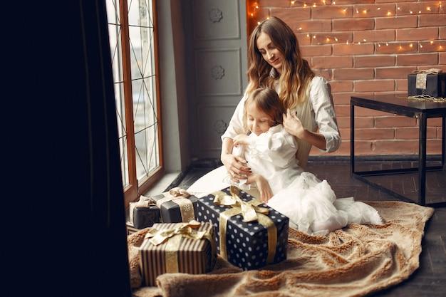 Moeder met schattige dochter thuis in de buurt van venster