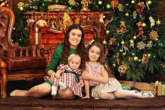 Moeder met schattige kleine dochters die op de vloer zitten in de kamer die is versierd met kerstvakantie