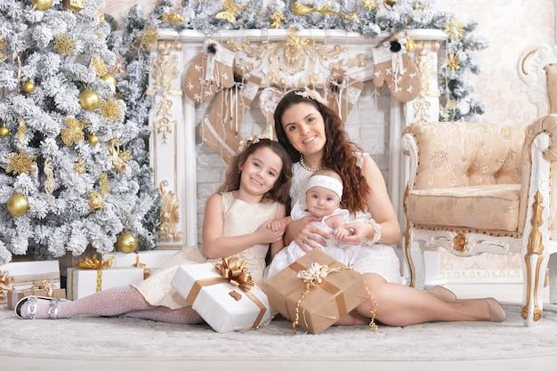 Moeder met schattige kleine dochters poseren in kamer ingericht voor kerstvakantie