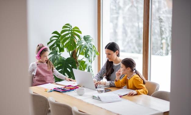 Moeder met schoolmeisjes binnenshuis, afstandsonderwijs en thuiskantoor coccept.