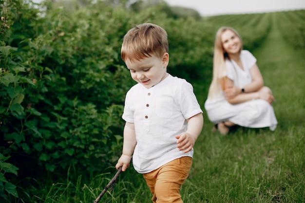 Moeder met sonplaying in een zomer veld