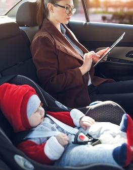 Moeder met tablet in haar handen en haar zoontje in een baby-autozitje rijden op de achterbank van een taxi