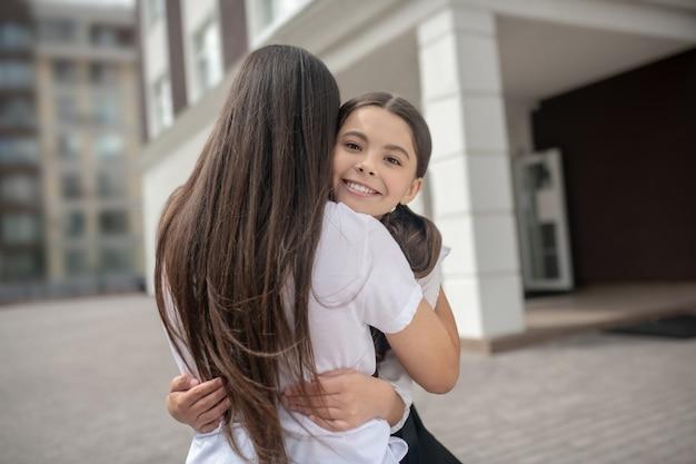 Moeder met terug naar camera en vrolijke dochter schoolmeisje knuffelen in de buurt van school