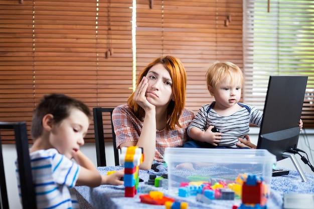 Moeder met twee jongetjes op zijn knieën probeert thuis te lachen. jonge vrouw zorgt voor kinderen en werkt op een computer.