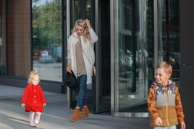 Moeder met twee kinderen bij de ingang van een kantoorpand of hotel gemaakt van glas en staal met een weerspiegeling van de lucht en een draaideur.