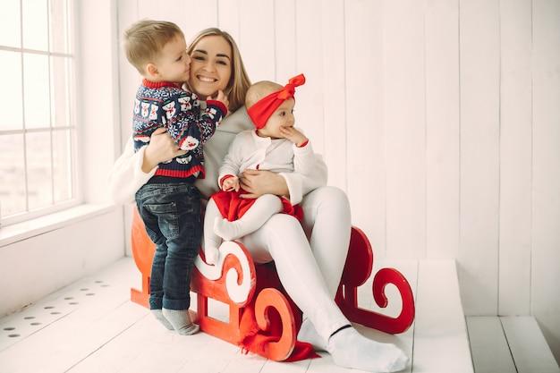 Moeder met twee kinderen die in een slee zitten