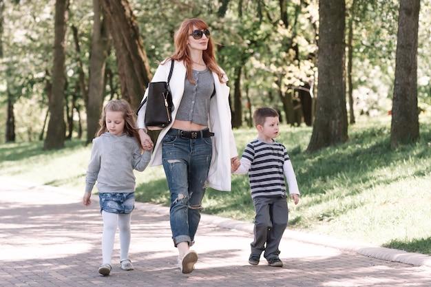 Moeder met twee kinderen die in het stadspark lopen. stadsleven
