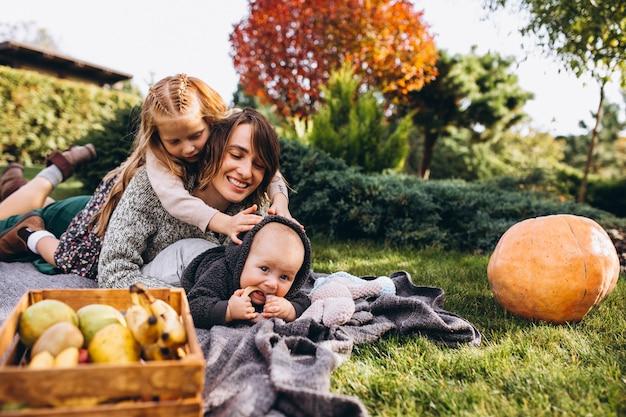 Moeder met twee kinderen met picknick op een achtertuin