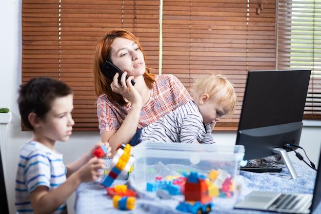 Moeder met twee kleine jongens op zijn knieën probeert thuis te lachen.