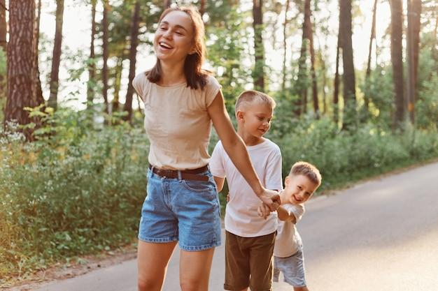 Moeder met twee zoontjes die buiten in de natuur spelen, donkerharige vrouw in t-shirt en korte tijd doorbrengen met haar kinderen op zonnige zomerdag, familie, jeugd.