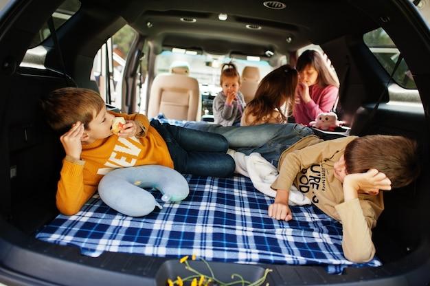 Moeder met vier kinderen bij voertuiginterieur. kinderen in de kofferbak. reizen met de auto, liegen en plezier maken, sfeerconcept.