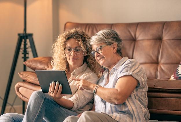 Moeder met volwassen dochter die thuis plezier heeft en samen nieuws deelt op een digitaal apparaat