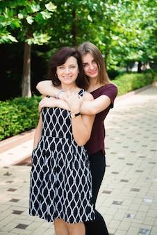 Moeder met volwassen dochter in park samen.