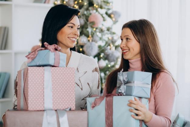 Moeder met volwassen dochter met kerstcadeautjes door kerstboom