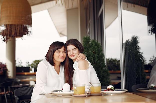Moeder met volwassen dochterzitting in een koffie