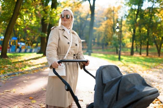 Moeder met wandelwagen loopt in het herfstpark