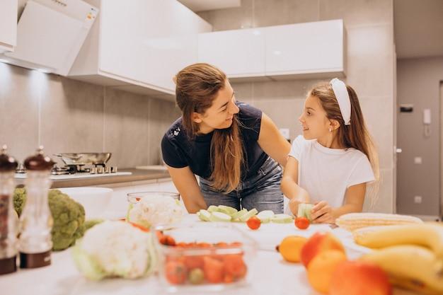 Moeder met weinig dochter die samen bij keuken koken