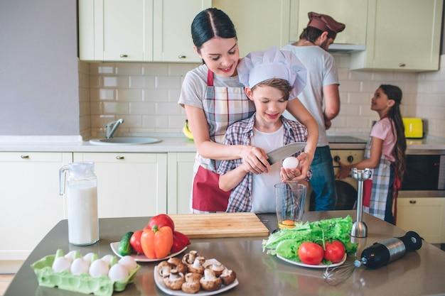 Moeder met zoon breken samen ei met mes. ze gaan het mixen. meisje helpt zijn vader om te koken op fornuis. ze kijken elkaar aan.