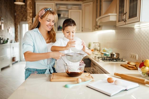 Moeder met zoon die gesmolten chocolade in een kom mengt