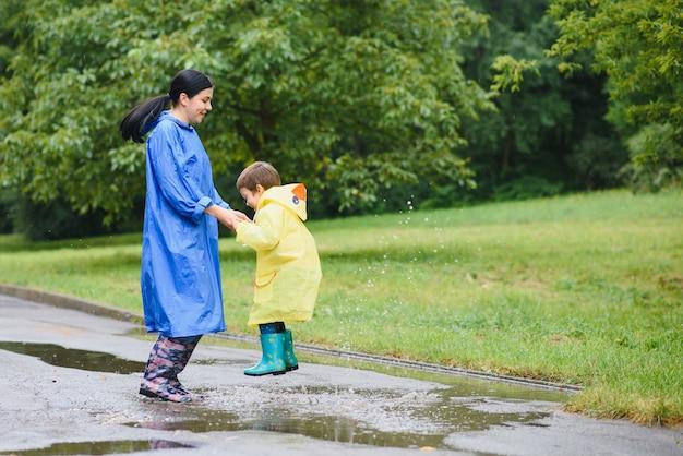 Moeder met zoon die in park in de regen lopen die rubberlaarzen draagt