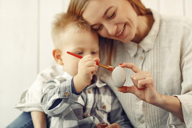 Moeder met zoon die thuis aan pasen voorbereidingen treft