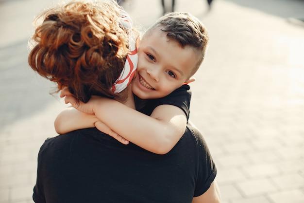 Moeder met zoon het spelen in een de zomerstad