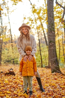 Moeder met zoon in de herfst bos, portret van familie poseren