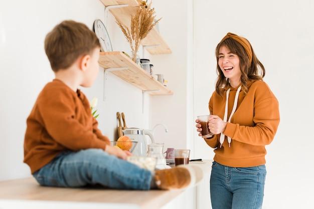 Moeder met zoon in de keuken genieten van de tijd samen