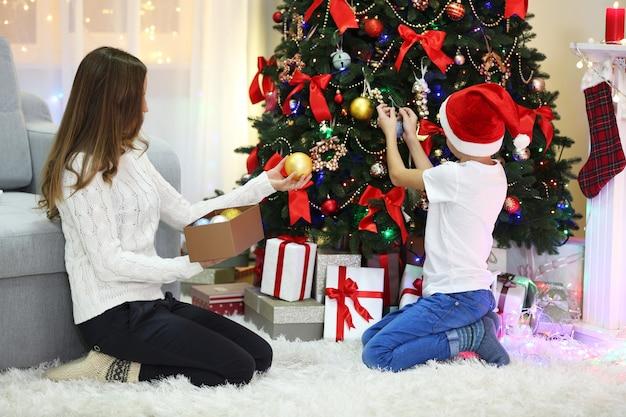 Moeder met zoon kerstboom versieren
