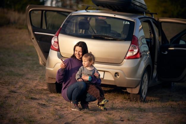 Moeder met zoon kijken naar zonsondergang tijdens het reizen met de auto