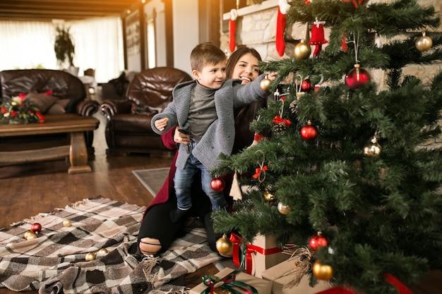 Moeder met zoon op kerstmis door de spar