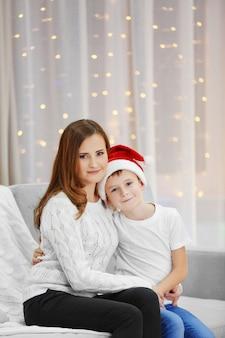 Moeder met zoon zittend op de bank in feestelijke kerstboom