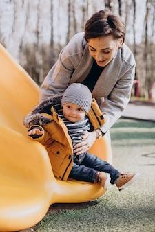Moeder met zoontje plezier op speelplaats