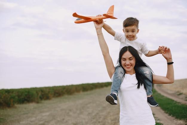 Moeder met zoontje spelen met speelgoed vliegtuig