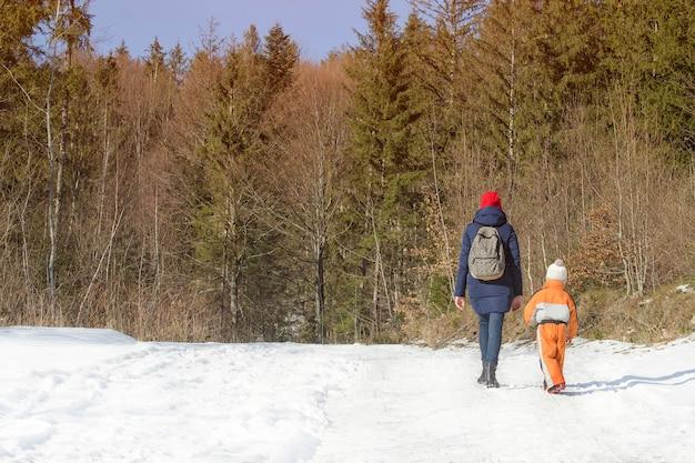 Moeder met zoontje wandelen langs besneeuwde weg