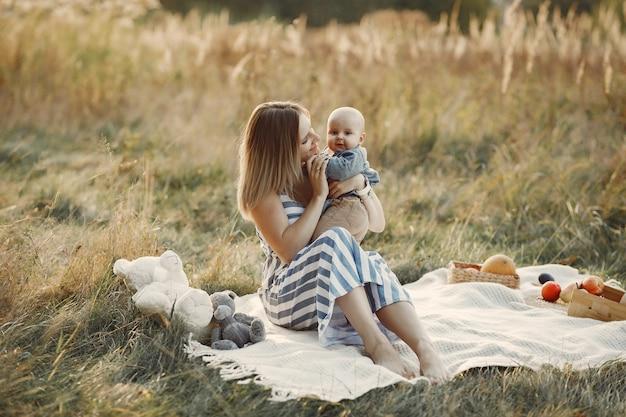Moeder met zoontje zit in een herfst veld