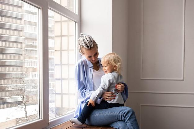 Moeder met zoontje, zittend bij het raam en spelen