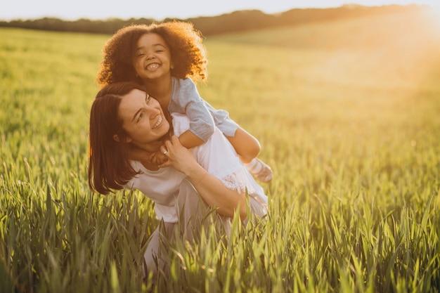 Moeder met zwarte babymeisje die samen plezier hebben in het veld
