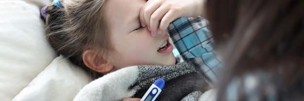 Moeder meten temperatuur van ziek meisje met thermometer