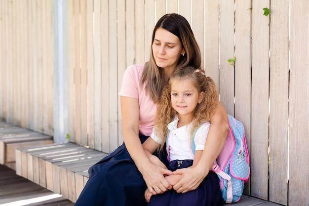 Moeder-moeder met kind naar school. het leerlingsmeisje van de basisschool gaat in openlucht met blauwe rugzak studeren. terug naar school. eerste herfstdag. basischoolleerling.