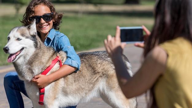 Moeder neemt een foto van zoon met hond in het park