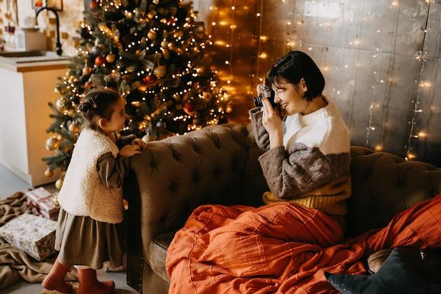 Moeder neemt foto's van haar dochter thuis, naast een kerstboom