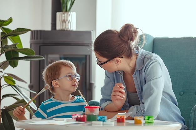 Moeder of beeldend therapeut en kind schilderen samen aquarel