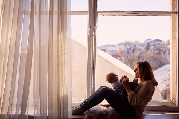 Moeder omarmt haar zoon en gaat bij het raam zitten